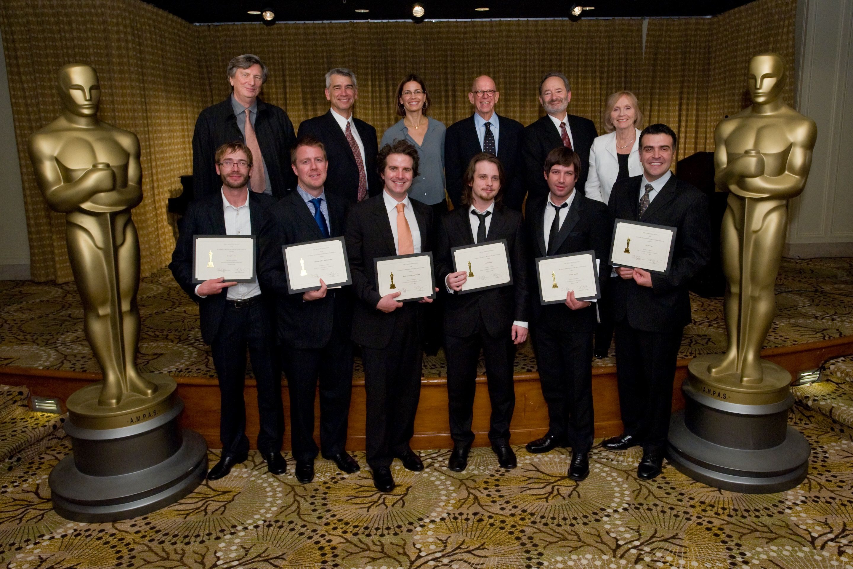 (left to right, front row) Jeremy Bandow, Colin Marshall, Ken Kristensen, Lee Patterson, Jason Miscallef, Eric Nazarian. Nicholl Fellowship Committee: (back row) John Bailey; David Nicksay;  Susannah Grant, Robert Shapiro, Peter Samuelson, Eva Marie Saint