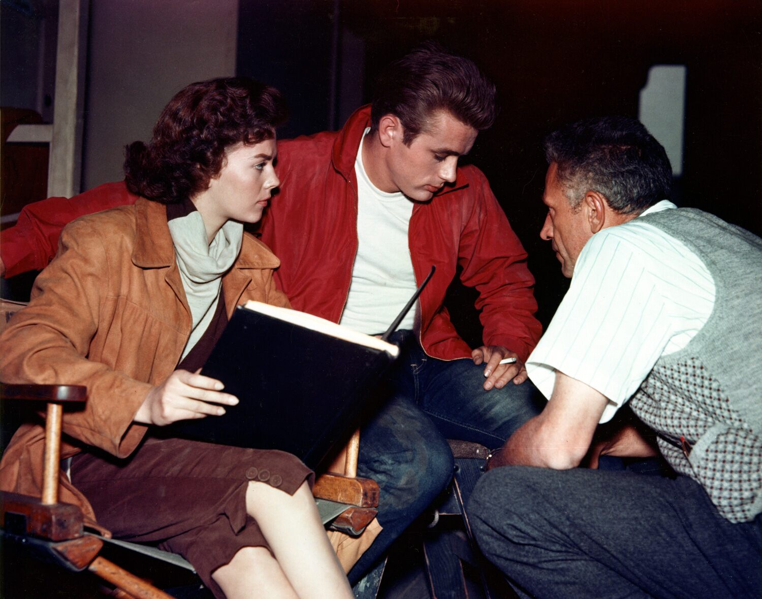 The filmmaker consults with James Dean and Natalie Wood during production of Rebel without a Cause. The film was started in black and white but switched to color and CinemaScope early in production.