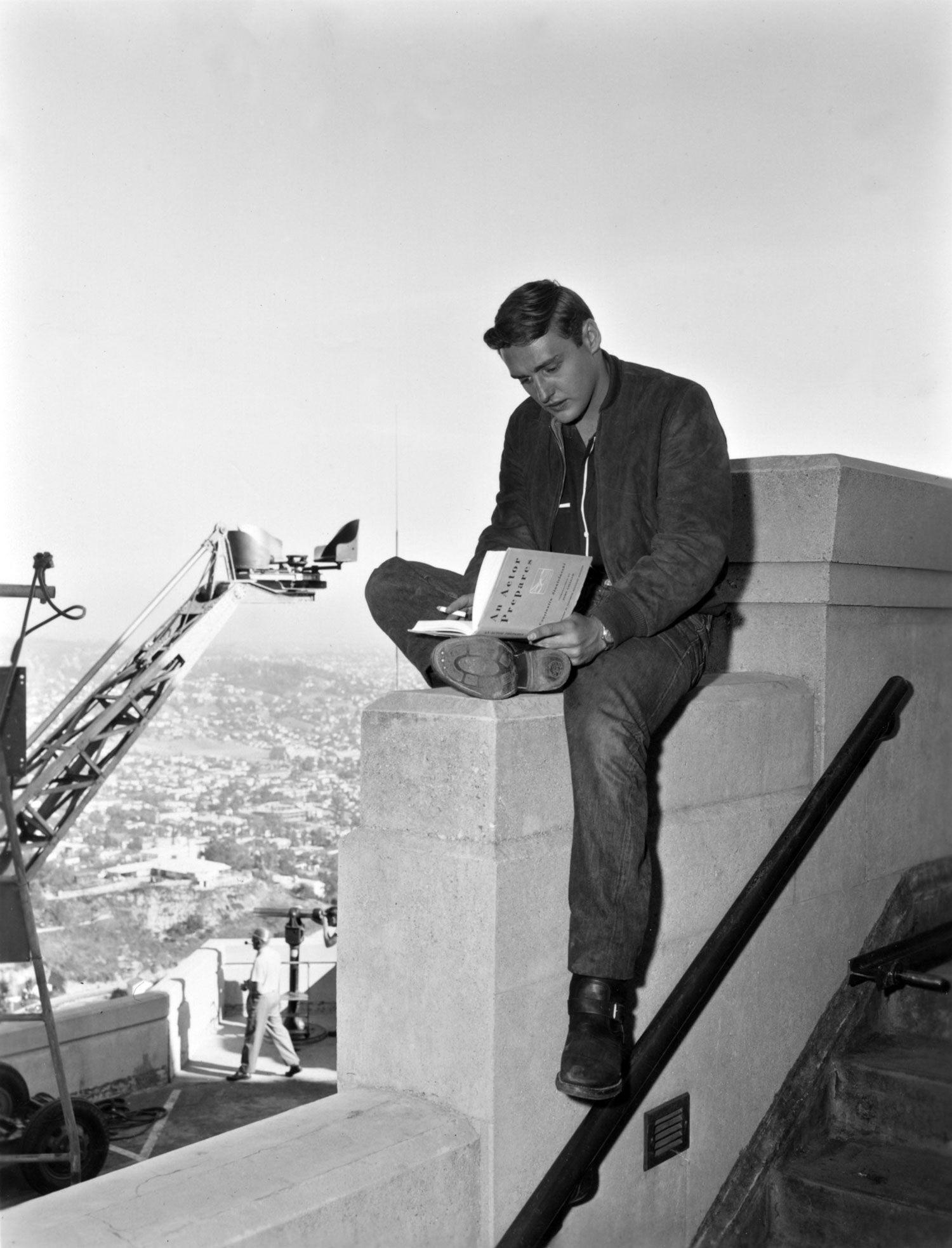 The actor enjoys some reading time while filming the rumble scene atop the Griffith Observatory in Rebel without a Cause.