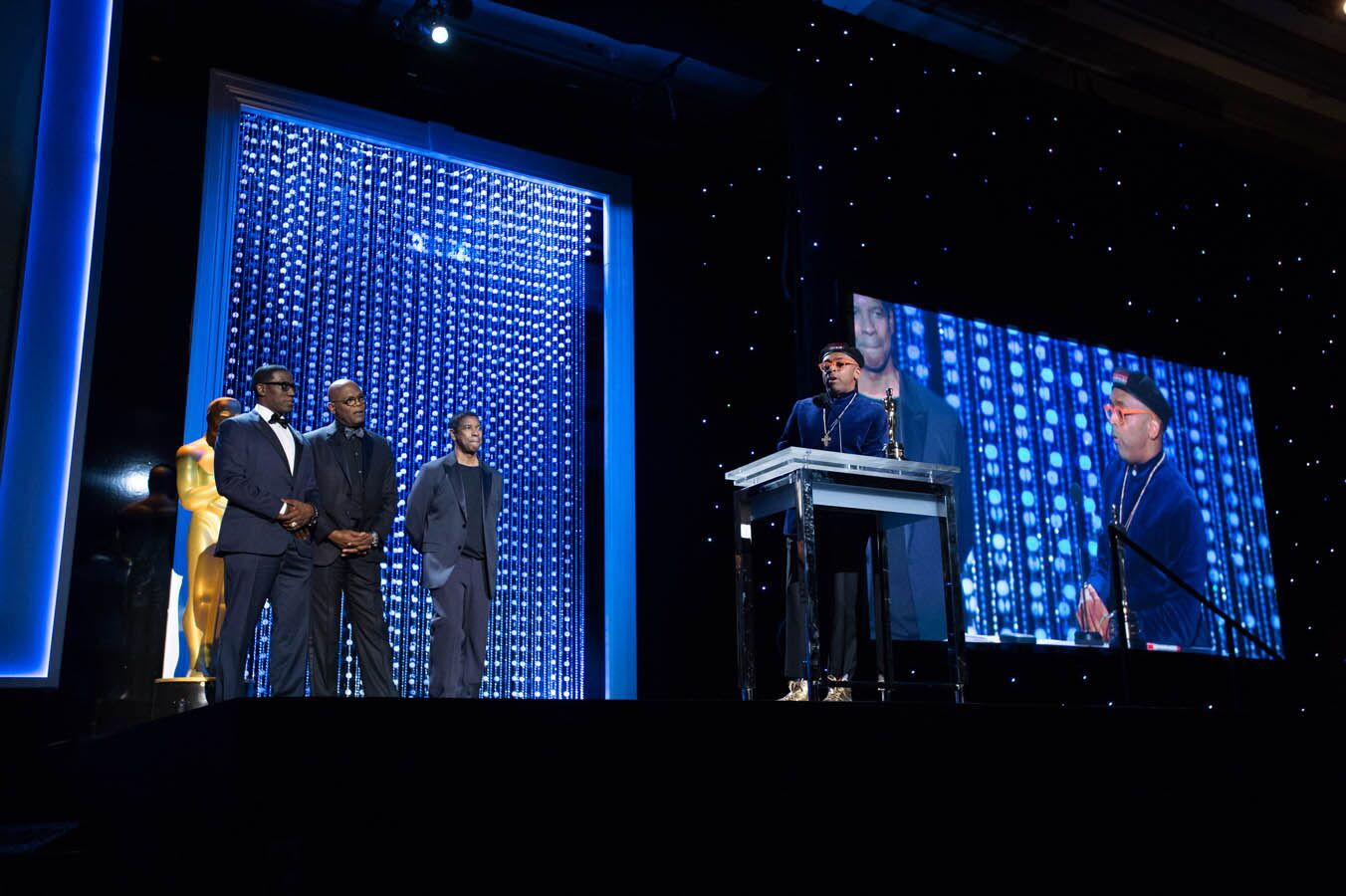 Actor Wesley Snipes, Oscar®-nominated actor Samuel Jackson and Oscar-winning actor Denzel Washington present the Oscar to Honorary Award recipient Spike Lee at the 2015 Governors Awards