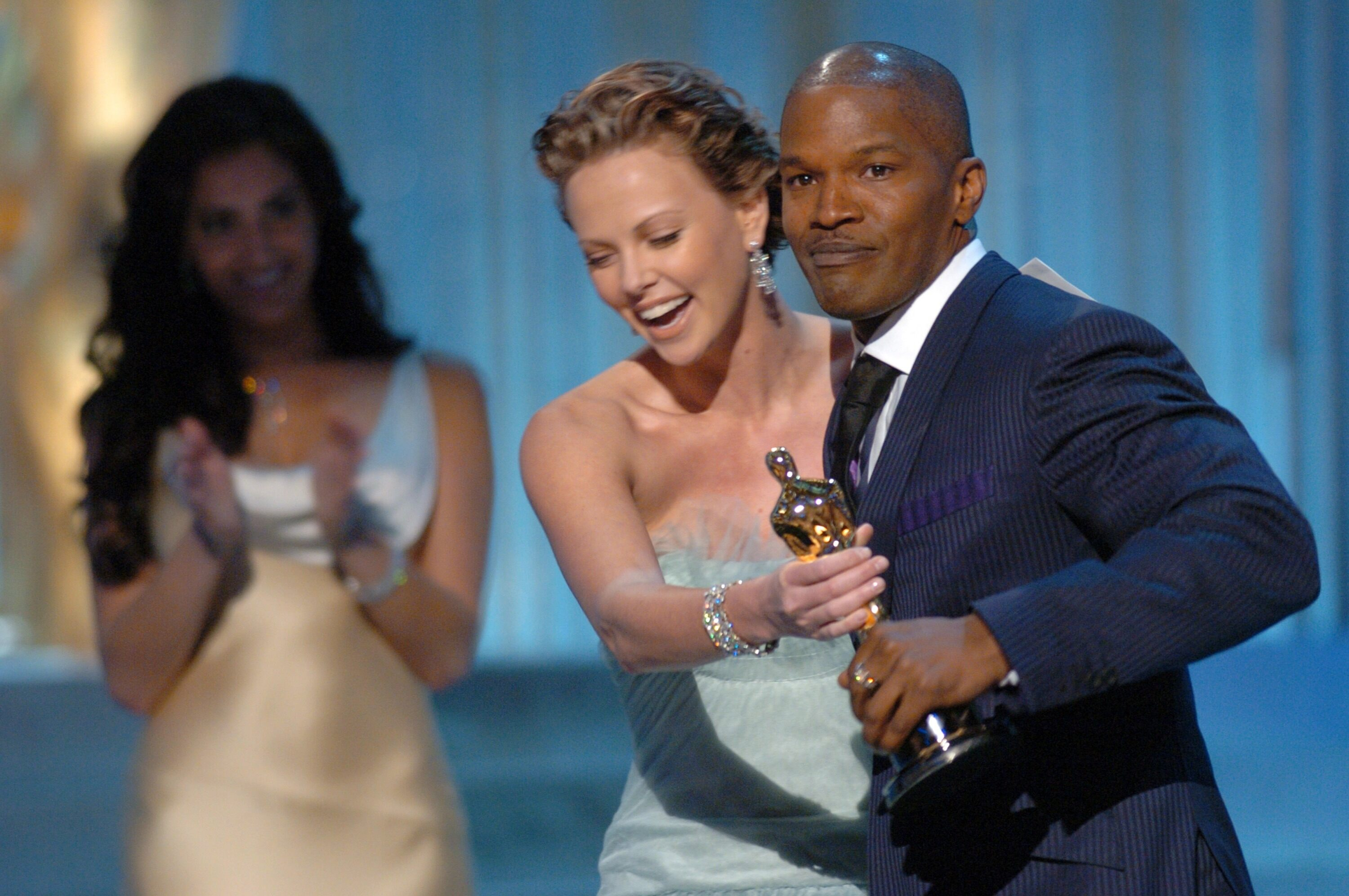 Jamie Foxx accepts the Academy Award for Best Actor from Oscar winner Charlize Theron.
