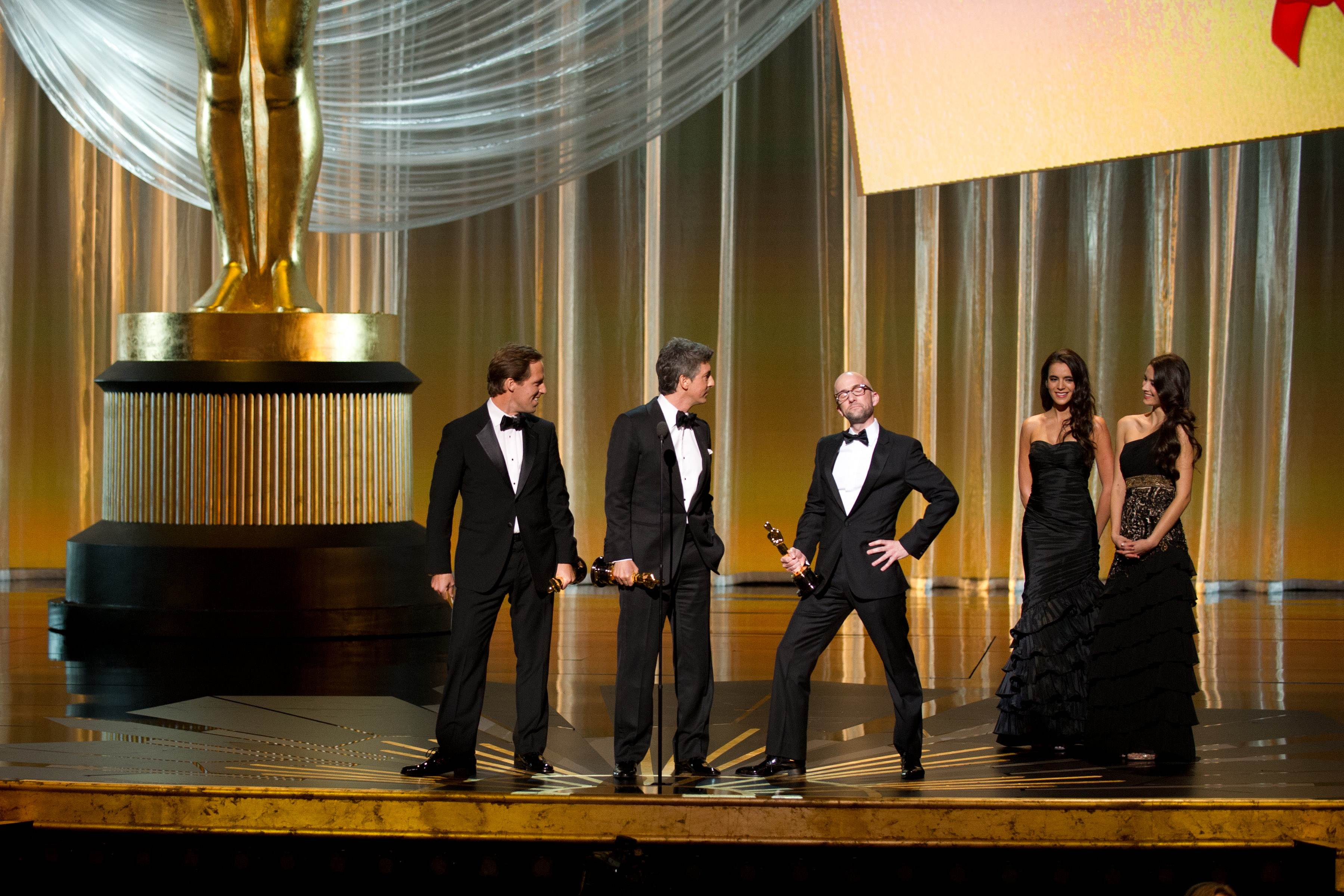 """Alexander Payne, Nat Faxon and Jim Rash accept the Oscar® for Adapted Screenplay for work on """"The Descendants,"""" while Jim Rash takes the opportunity to imitate Angelina Jolie's """"leg pose."""""""