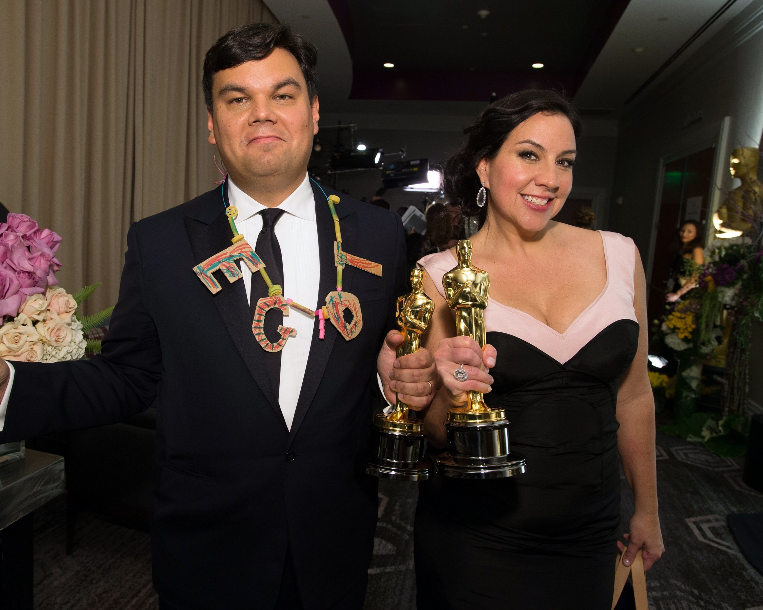 "fter winning the category Achievement in music written for motion pictures (Original song) for ""Let It Go"" from ""Frozen"", Kristen Anderson-Lopez and Robert Lopez pose."