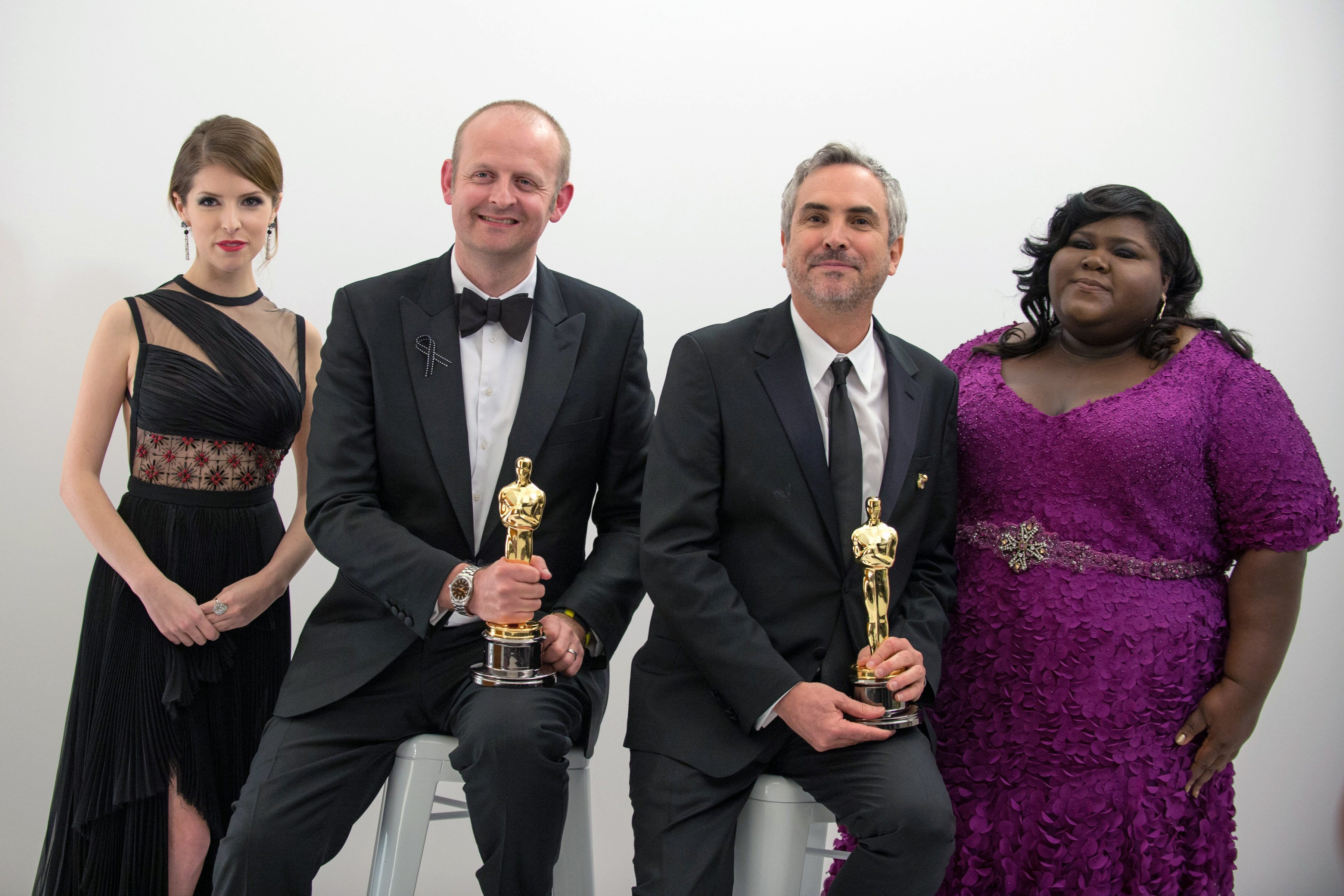 "After winning the category Achievement in film editing for work on ""Gravity"", Alfonso Cuarón and Mark Sanger pose backstage with their Oscar® and Anna Kendrick (left) and Gabourey Sidibe (right)."