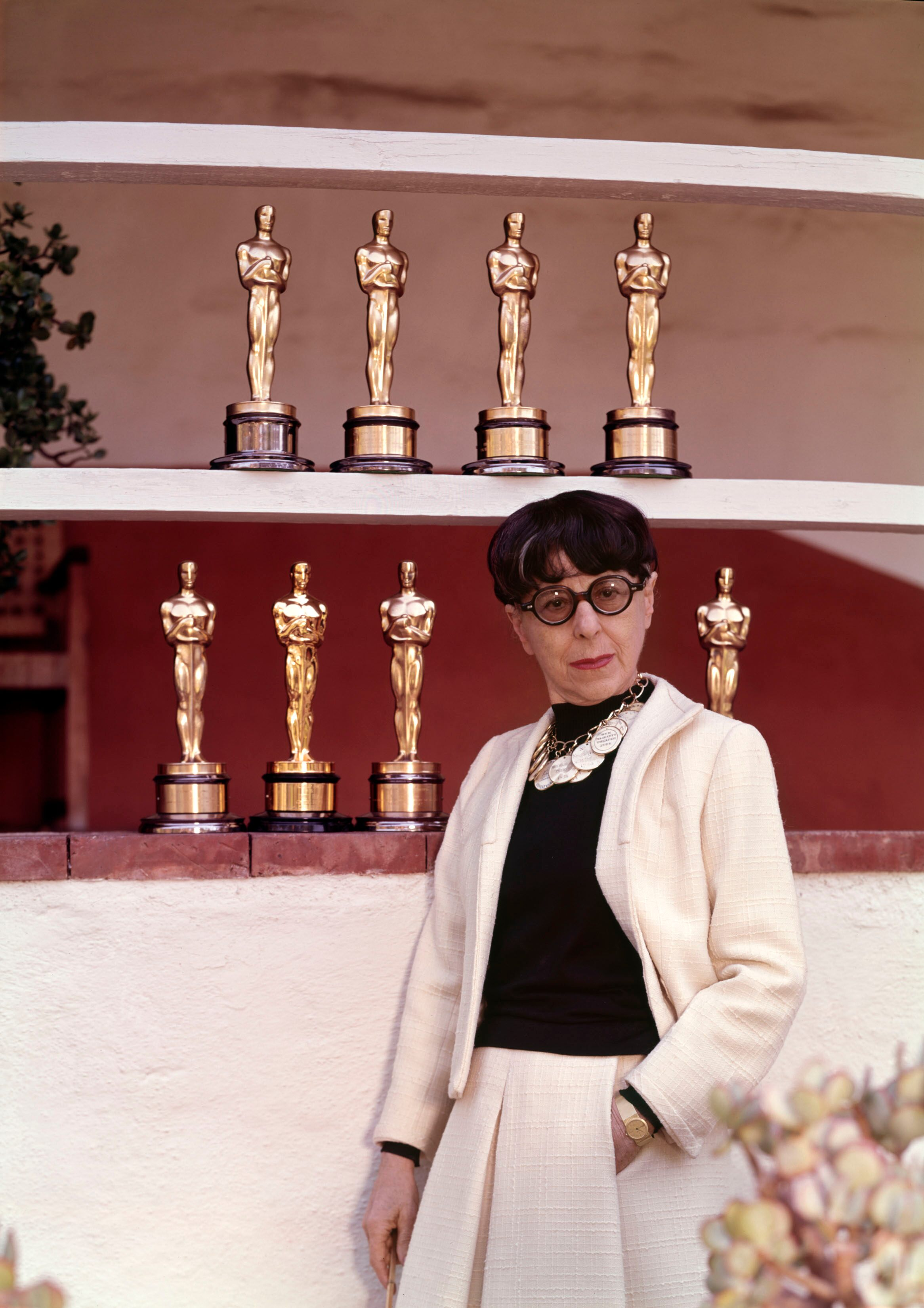 Posing with her eight Academy Award statuettes, Edith Head still holds a record in the Costume Design category.