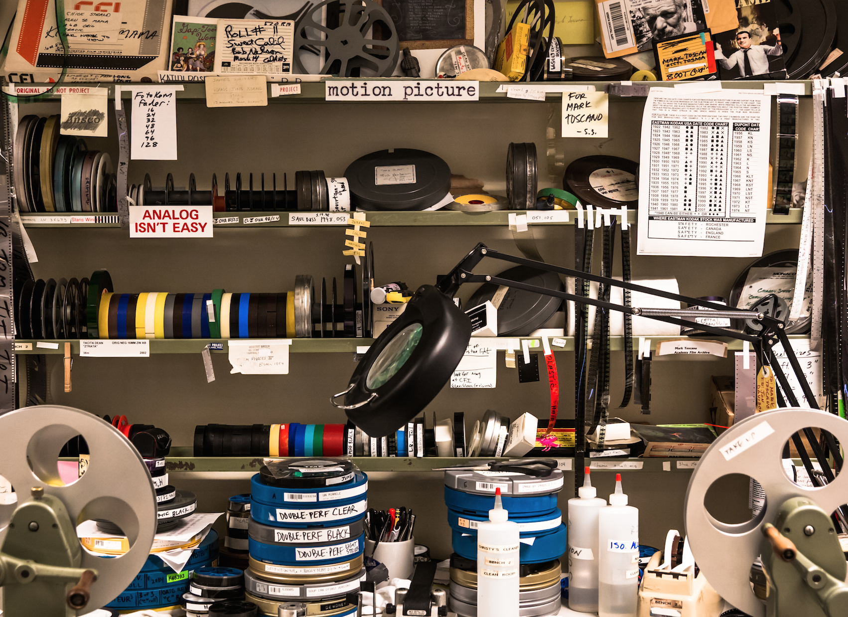 Preservationist workstation featuring film cleaner, film splicers, film tape, various film leaders, split reels, cores, and film cans