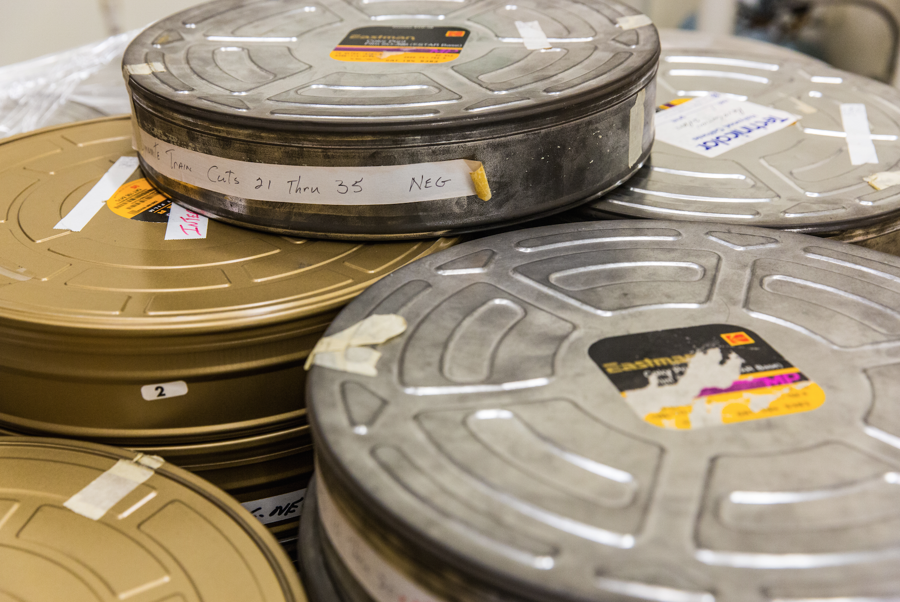 Stacks of 70mm film cans, waiting to be inventoried, catalogued, and placed in new archival cans